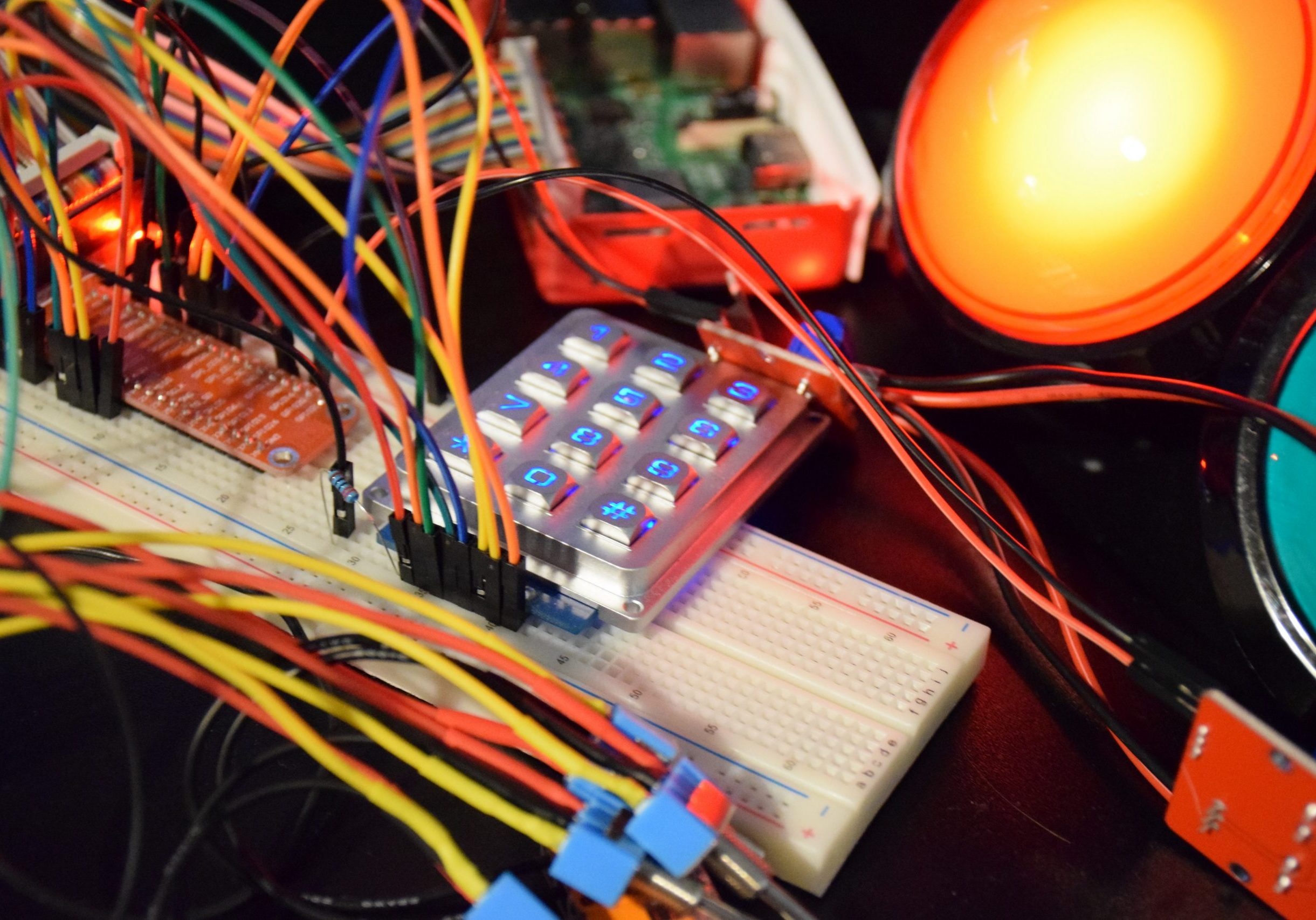 Photograph of Raspberry Pi project development with various components all connected together, such as keypad, LED lights and toggle switches