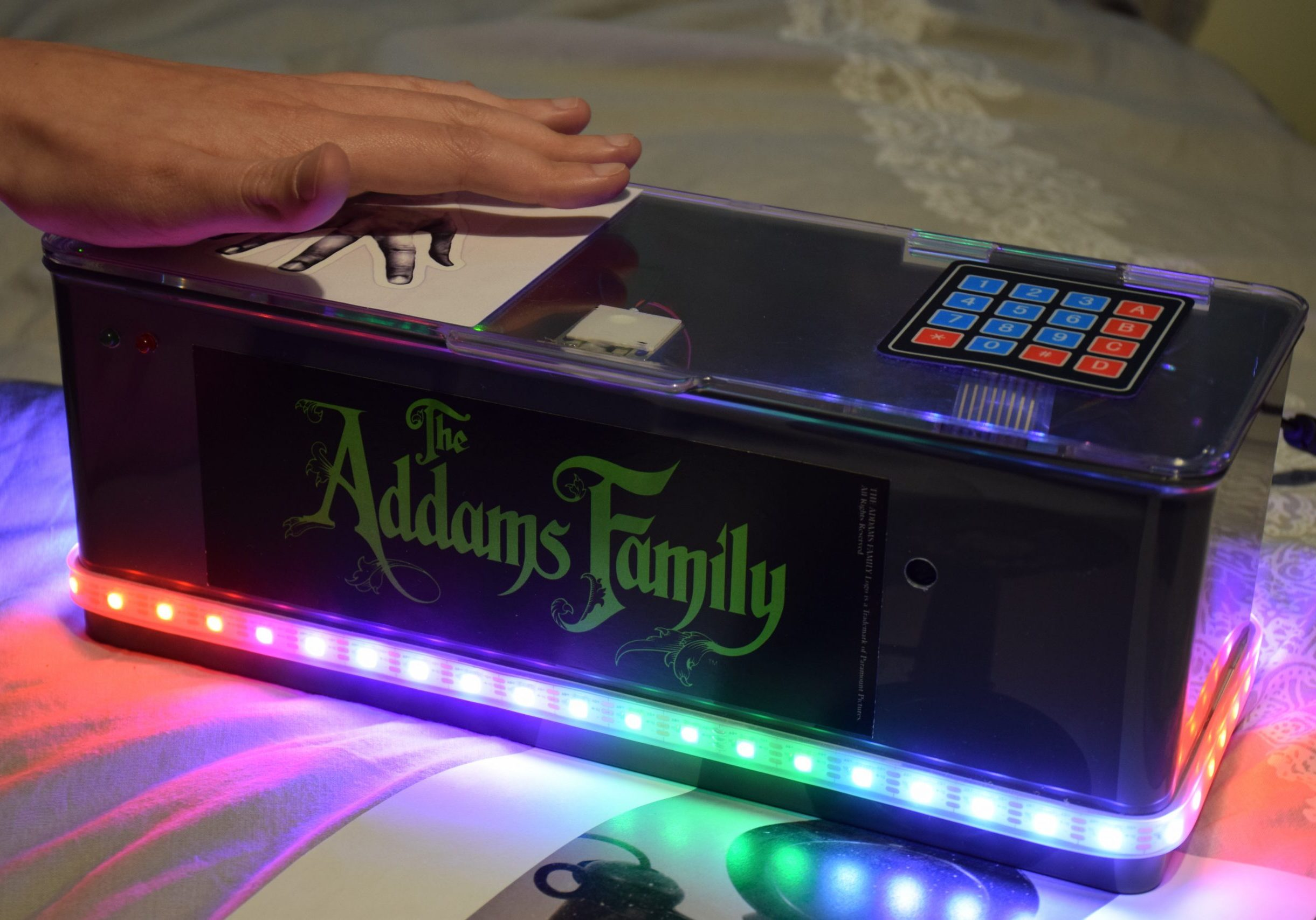 Photograph of puzzle box with Addams Family label on front and strip of coloured LED lights illuminated with matrix keypad and image of hand on top being controlled by a users hand