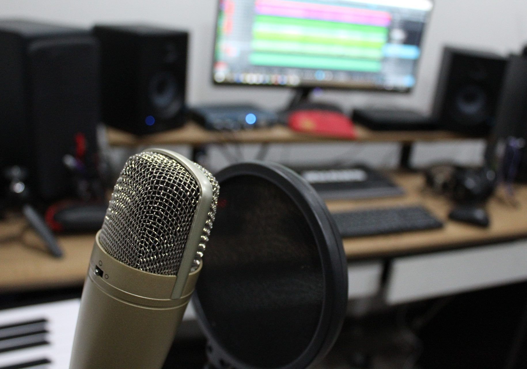 Photograph of a microphone in front of a pop filter with a recording studio in the background