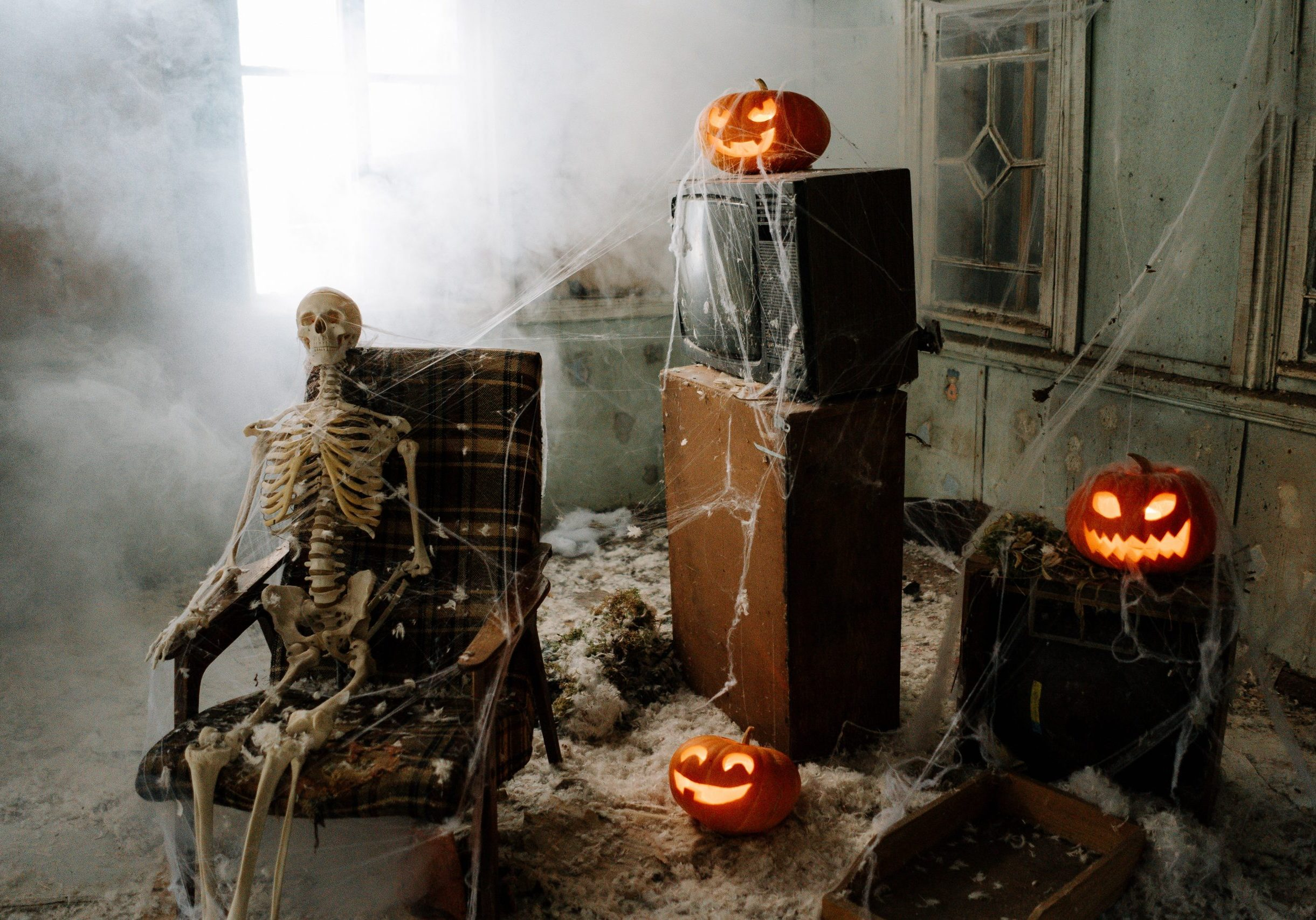 Photograph of halloween haunt attraction with skeleton, jack o'lantern and tube TV, all covered in spider cob webs