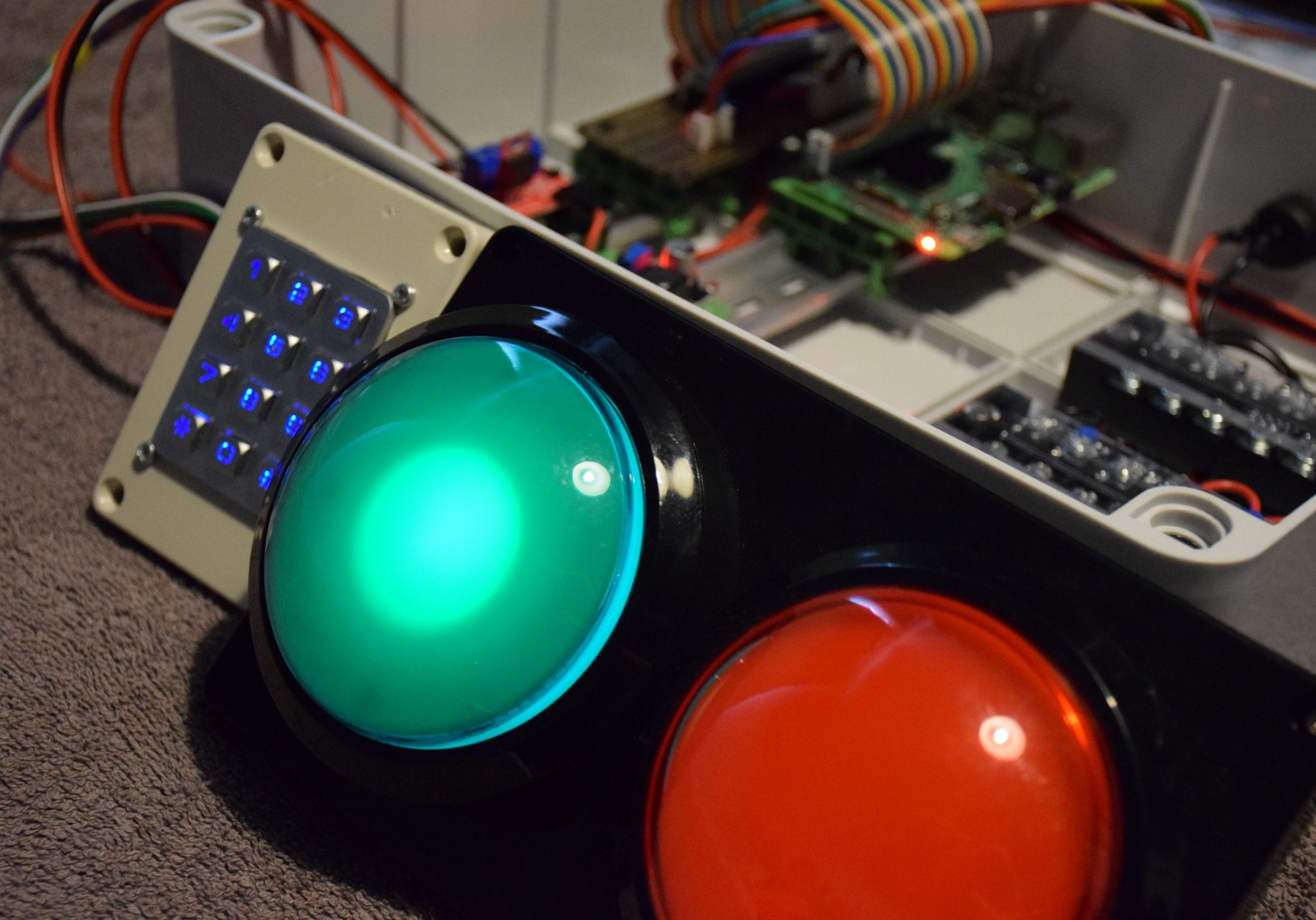 Photograph of illuminated keypad with large green and red LED lights which are in front of a box of cabled components