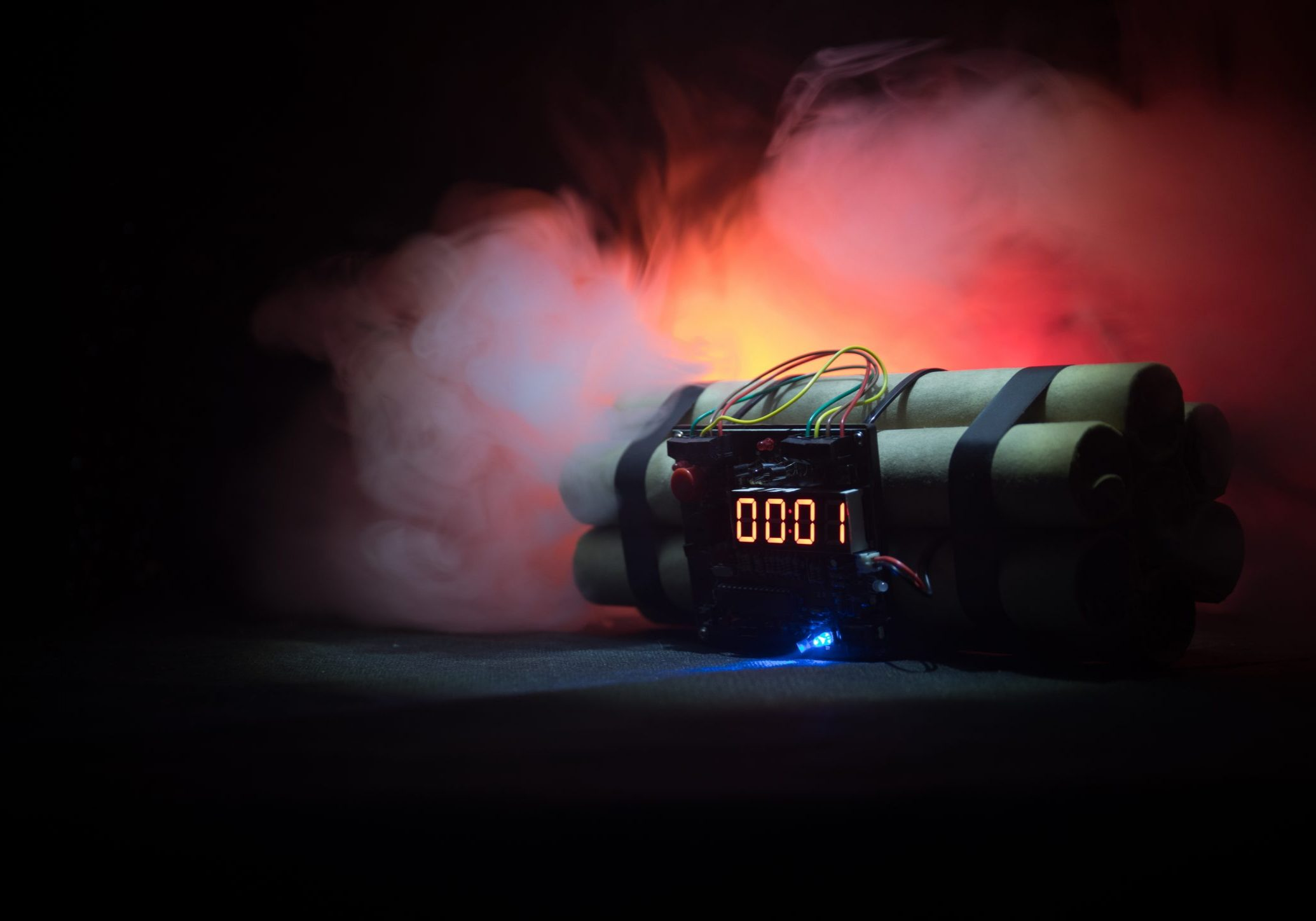 Photograph of a prop of dynamite with a countdown timer on the front and red smoke in the background